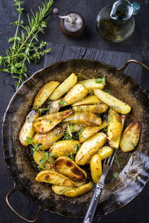 Roast Potatoes with herbs as top view in an iron cast pan