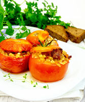 Tomatoes stuffed with bulgur in plate on light board