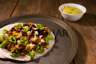 Mexican tortillas with meat, red beans, Jalapeno pepper and salsa guacamole