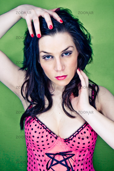 pin-up picture of sexy lady inpink corset on green background