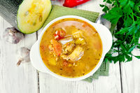 Soup fish with zucchini and peppers on board top