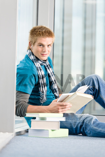 Young man with earbuds and books