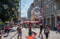 Girl making soap bubbles on a sunny day on the street in Berli