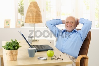 Happy elderly man smiling at desk