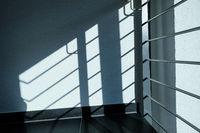 Geländer im Treppenhaus als Schatten auf Wand