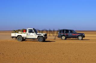 Jeeps fauf einer Pistenstrasse in der Wüste