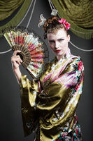 Beautiful young woman as geisha with fan