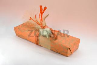 Geschenkverpackung in orange mit Feder