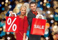 couple with sale and discount sign on shopping bag