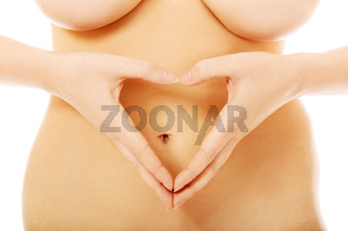 Woman making heart shape with her hands on her belly