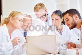 Ärzte Team schaut auf Licht aus Laptop Computer