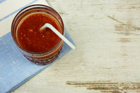 A glass of fresh tomato juice with a straw on a napkin and an old wooden table