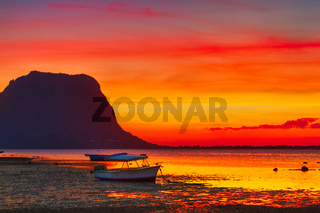 Fishing boat at sunset time. Le Morn Brabant on background.