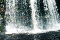 Feamale hiker, tourist, model standing or walking under the Sgwd Yr Eira Waterfall in Wales