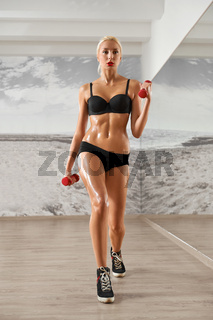 Sexy, athletic, blonde woman in the gym, against the background