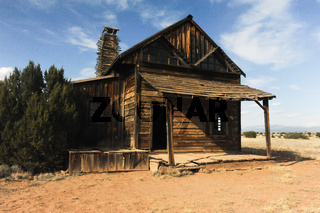 Old Fashioned wooden house with wood covered porch in country of New Mexico.