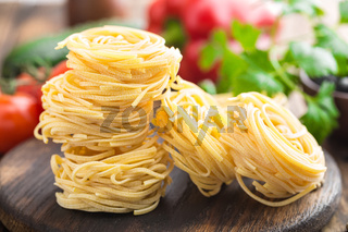 Raw all'uovo pasta, egg noodles with cooking ingredients on dark wooden rustic background, traditional italian cuisine