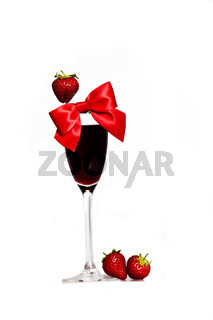 decorated glass of red wine with red ribbon and fresh strawberries