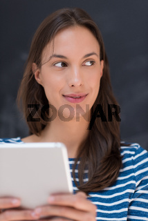 woman using tablet  in front of chalk drawing board