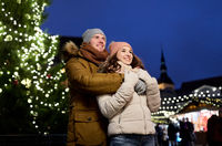 happy couple hugging at christmas tree