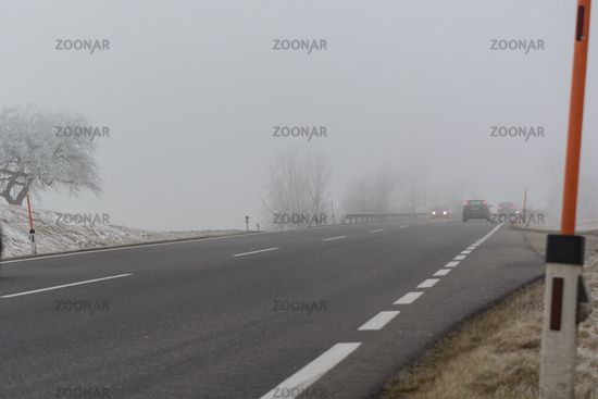 Cars drive in the fog on slippery road