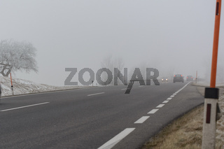Autos fahren im Nebel auf rutschiger Strasse