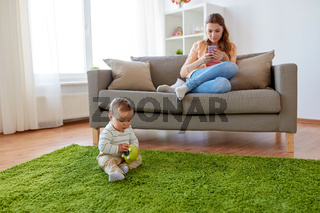 mother with smartphone and baby playing at home