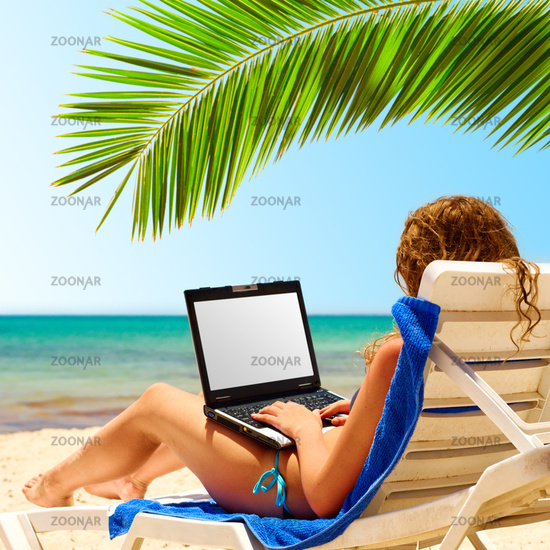 surfing on the beach. Laptop display is cut with clipping path