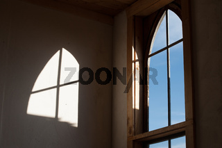 Old-fashioned church window with sunlight reflecting on wall of interior of church.