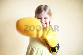 Little girl with yellow boxing gloves over yellow wall background