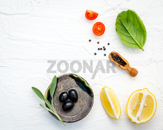 Food background with fresh herbs  tomato ,lemon slice , black pepper ,sage leaves ,sweet basil and olive oil over white wooden background  with flat lay and copy space.
