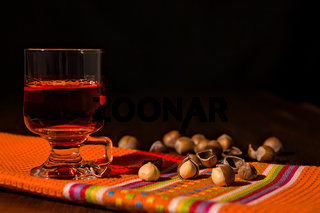 Glass of alcoholic punch drink and hazelnuts