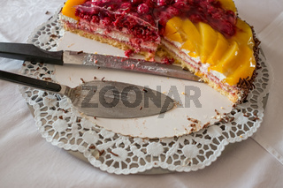 Tortenheber und Messer auf Kuchenplatte mit Obsttorte