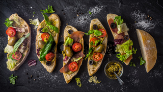 Slices of ciabatta with olives , tomatoes and basil on the black stone table wide screen