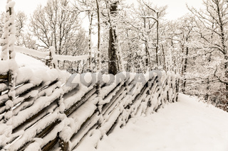 Roundpole fence covered in snow, winter in Norway