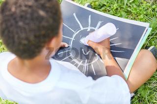 Junge malt mit Kreide das Bild einer Sonne