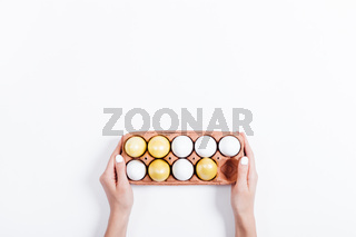 Female hands holding a tray with yellow Easter eggs on white background