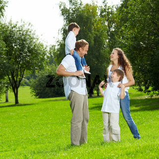Laughing family with two sons walks in a summer garden