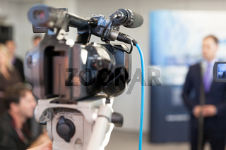 Video camera in focus, blurred spokesperson in background