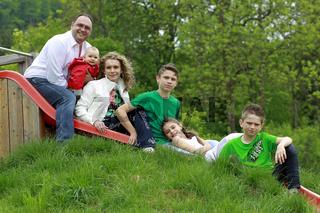 Familie sitzt auf einer Kinderrutsche