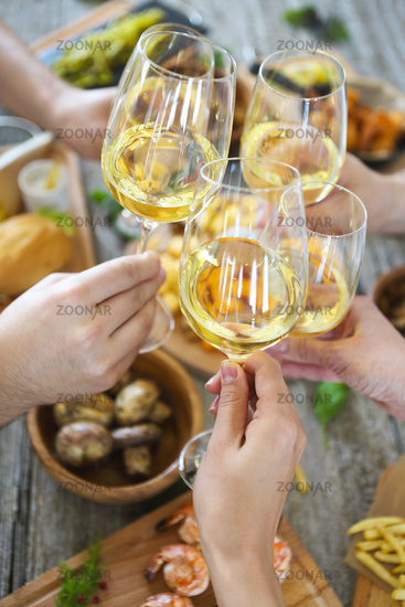 People with white wine toasting over served table with food.