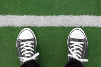 Sneakers at artificial green grass playground