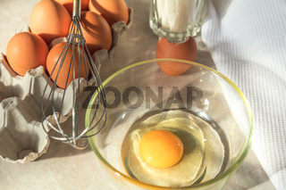 Broken egg in a glass bowl ready for whipping. Fresh chicken eggs in a cardboard tray, whisk and white towel on a kitchen table