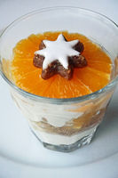 Dessert in wintertime with cinnamon star and orange