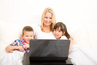 Mother with her kids using a laptop in bed