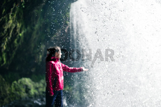Feamale hiker, tourist, model out of focus touching water under the Sgwd Yr Eira Waterfall in Wales