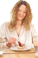 Junge Frau macht sich ein Marmeladenbrötchen