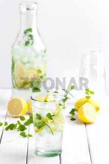 Citrus lemonade in a glass cup on a white wooden table.