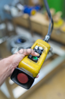 Industrial worker pushing on button of machinery controler.
