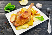 Duck leg with apple and basil in plate on board